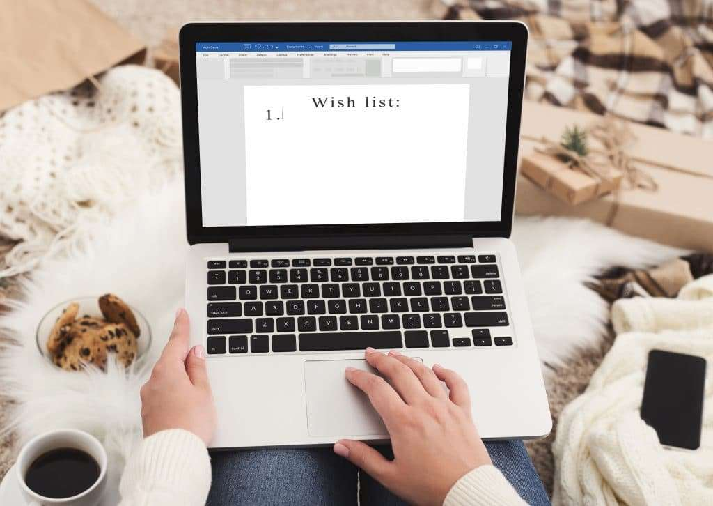 Woman writing Christmas list on laptop computer, sitting on plaid in cozy room with gift boxes around and drinking coffee, creative holiday background with copy space for your text - tech gifts