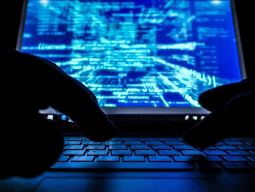 hands behind keyboard looking into cyber security,