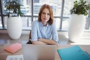 woman sitting behind a desk being the customer facing person, hiring strategy