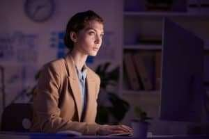 Serious Female Office Worker Using Computer getting work done, hard worker hiring strategy